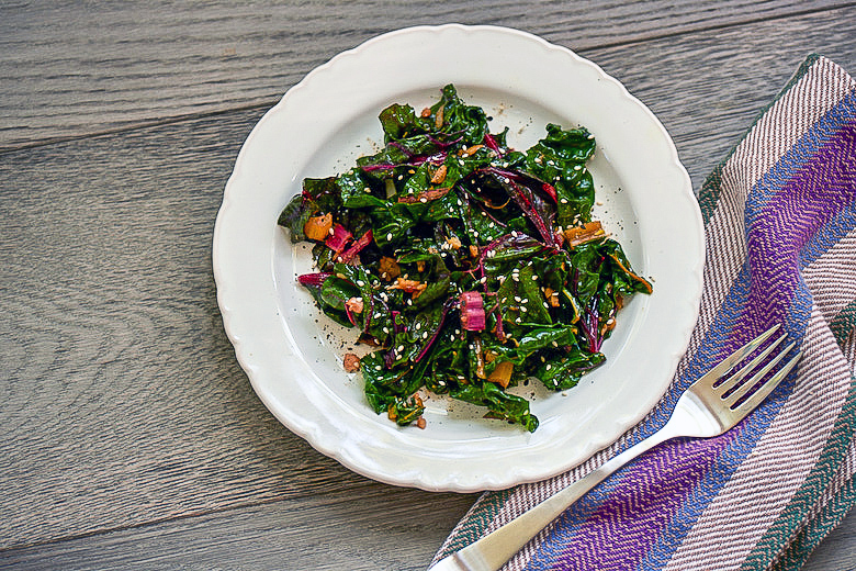 GarlickySwissChardwith Sesame Seaweed Sprinkle, on white plate on wooden background with napkin