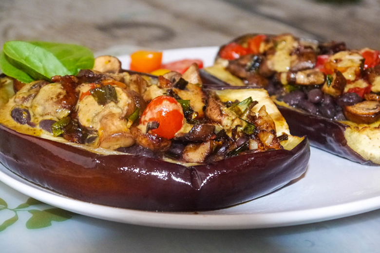 Vegetarian Stuffed Eggplant with Savory Pistachio Cream on a white plate on countertop