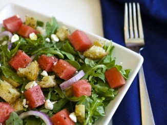 Watermelon panzanella salad in a square bowl with a fork