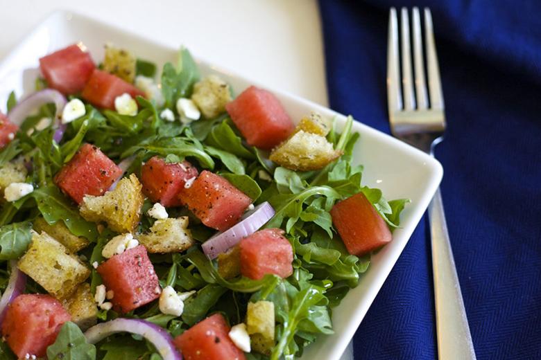 Watermelon panzanella salad in a square bowl with a fork