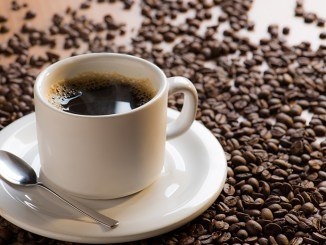a cup of coffee in a table full of coffee beans