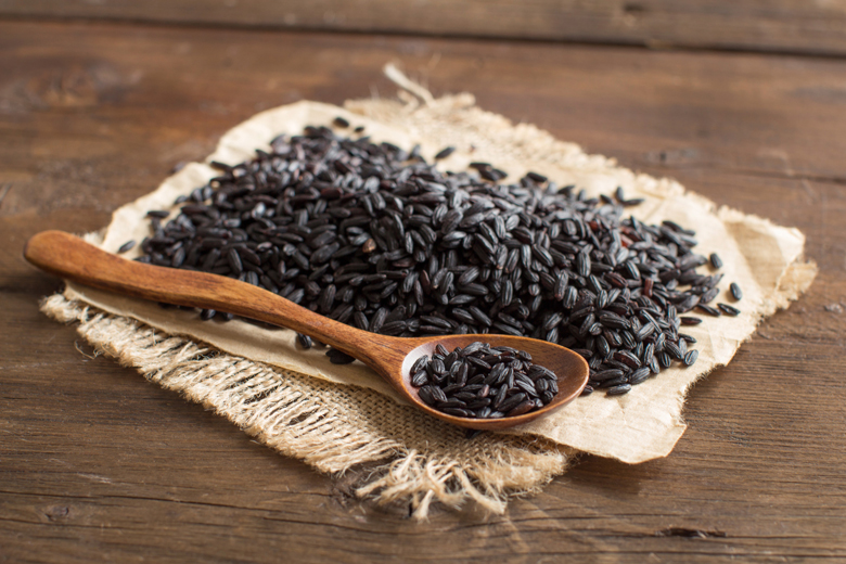 Pile of black rice with a spoon on a wooden table
