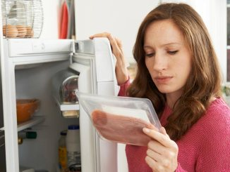 Woman looking at label of lunch meat with fridge open