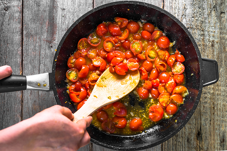 Person cooking dish with fried tomatoes, sauce for pasta, healthy food, italian meal preparing, detailed view of hands and pan, overhead