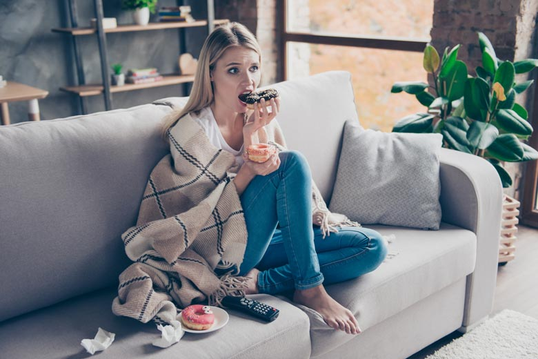 A blonde woman sits on a couch with a blanket wrapped around her eating a chocolate glazed donut