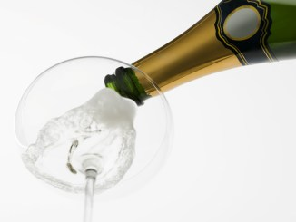Bottle of Champagne being poured into glass