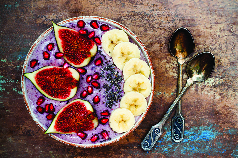 Healthy fall and winter breakfast set. Acai superfoods smoothies bowl with chia seeds, pomegranate, sliced banana, fresh figs and hazelnut butter.