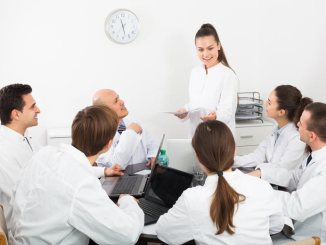 Young woman making presentation in front of colleagues