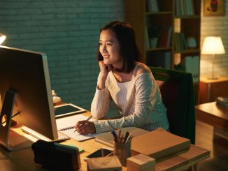 Asian woman sitting at a computer with a desk full of materials