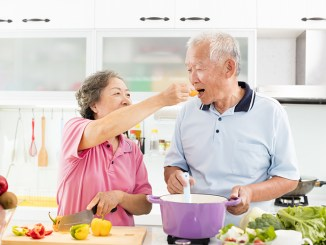 happy senior couple cooking in kitchen