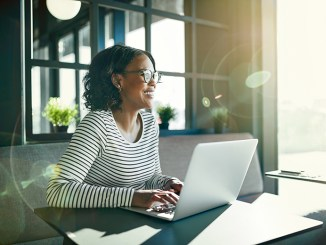 Smiling young African woman wearing glasses looking at laptop