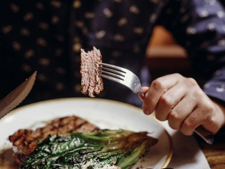 Hands holding fork and knife and eating