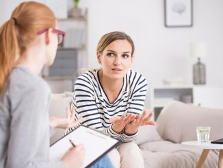 Two women dressed casually having a discussion. One holds a notepad and the other gesture with her hands.