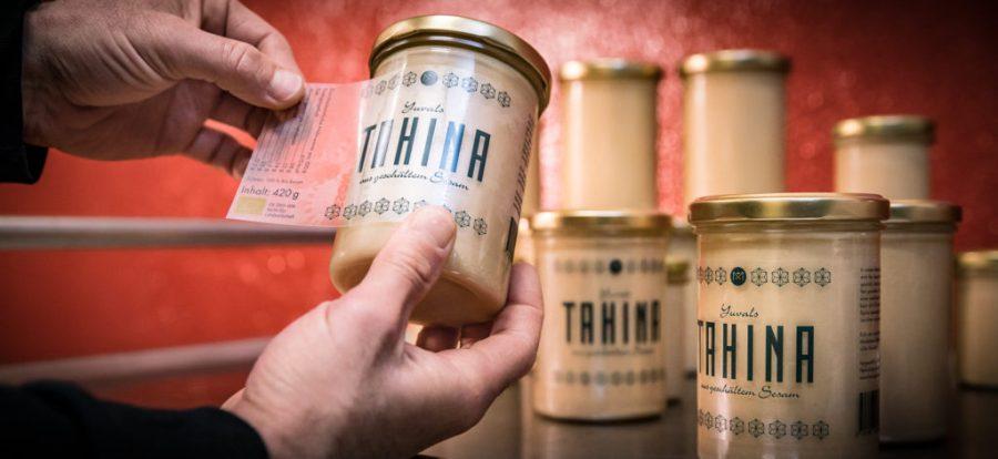 Yuval Königstein etikettiert seine fertige Tahina im Glas.