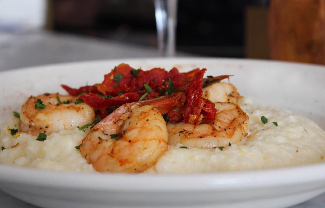 A bowl of girls topped with roasted shrimp and red peppers