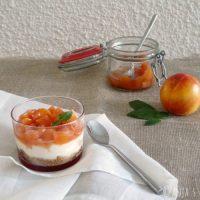 Delicious dessert: cheesecake in een glas met compôte van nectarine