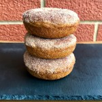Stack of 3 vegan pumpkin spice donuts with cinnamon sugar in front of a brick background