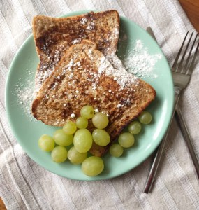 Cinnamon french toast with icing sugar and grapes
