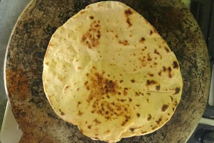 baking naan on a flat tawa