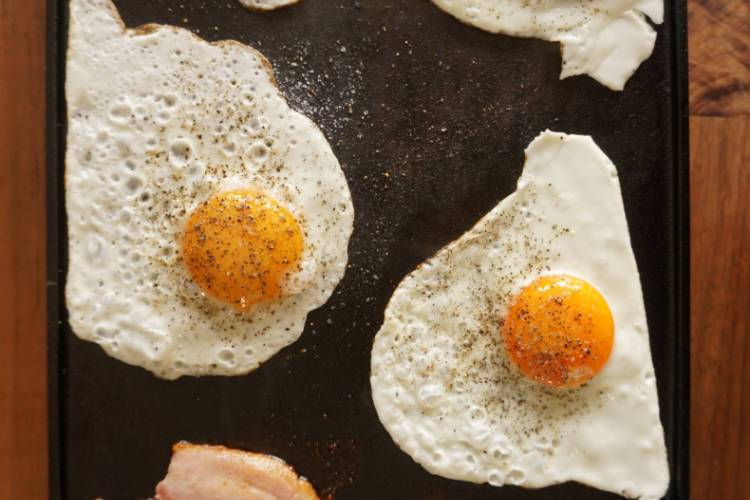 bacon and eggs, fried on a cast-iron griddle