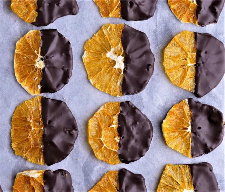 close up of dried round orange crisp slices half covered in dark chocolate on tray lined with white greaseproof paper