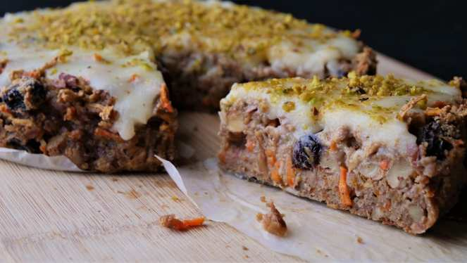 slice of carrot cake next to cake studded with raisins and carrots and topped with white frosting