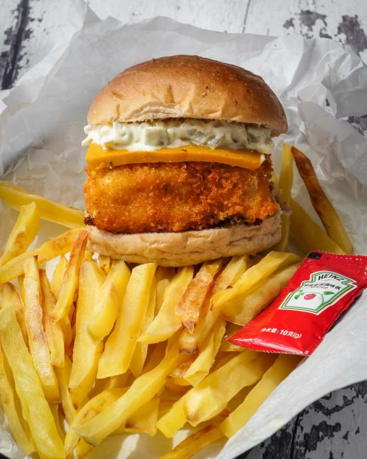 fried fillet coated in breadcrumbs in bread bun topped with cheese slice, gherkins, mayonnaise sitting on top of fries with ketchup
