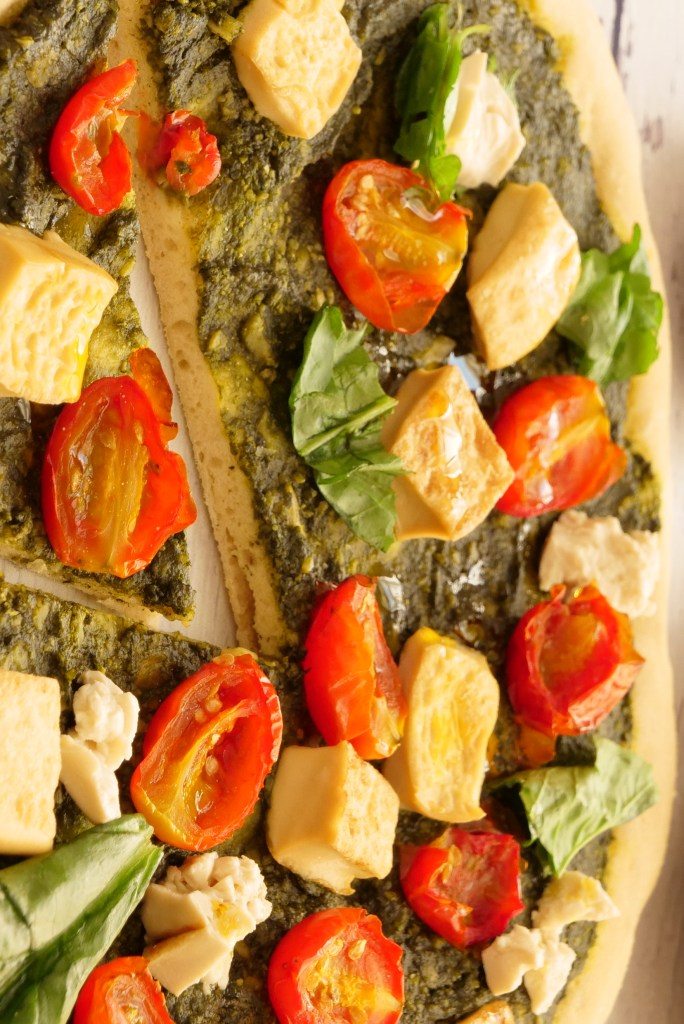 thin crispy italian pizza topped with tomatoes, tofu cubes, basil, pesto on white rustic wooden table next to various ingredients in rustic pottery