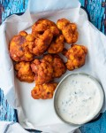 flatlay cauliflower buffalo wings on enamel tray lined with parchment paper next to pot of ranch on rustic blue wooden table