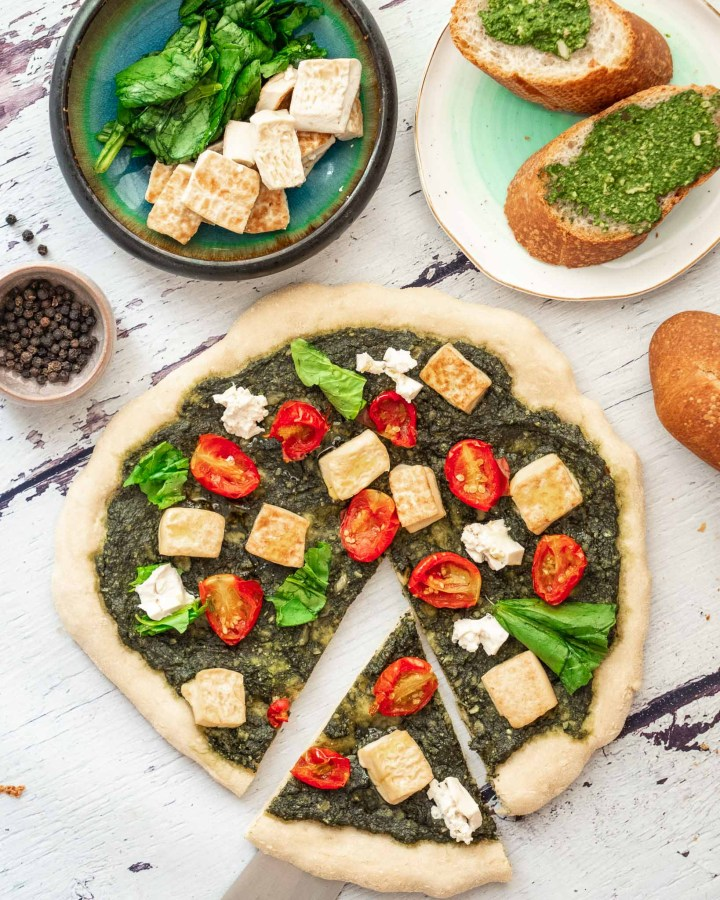 flatlay of pizza with spinach pesto, cherry tomatoes, tofu mozzarella, fresh basil on white wooden table next to garlic bread, and toppings in turquoise bowl