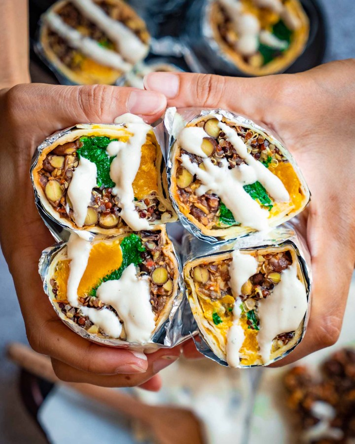 four black bean burritos cut in halves and held by hands drizzled with tahini sauce filled with beans, spinach and pumpkin