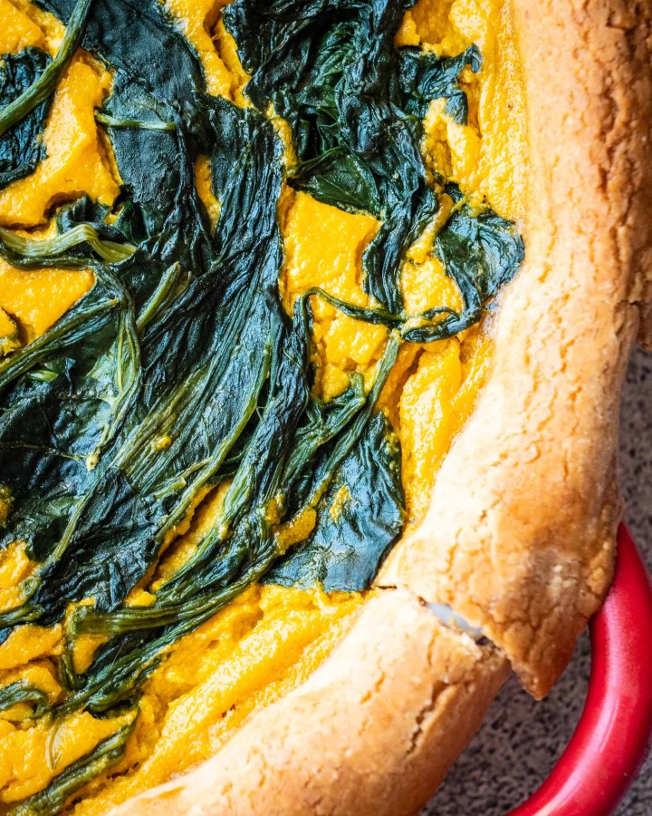 baked bright yellow vegan pumpkin cheese filling combined with wilted spinach in golden pastry shell in red flan dish