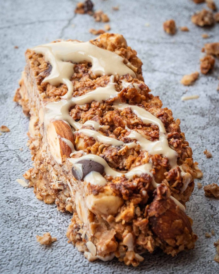 vegan granola bar drizzled with peanut butter and studded with almonds, hazelnuts and chocolate chips on grey stone surface