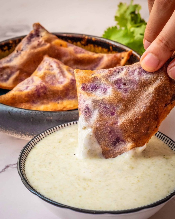 crispy triangle filled pastry samosa being dipped by hand into yoghurt next to pottery plate filled with more samosas on white marble top