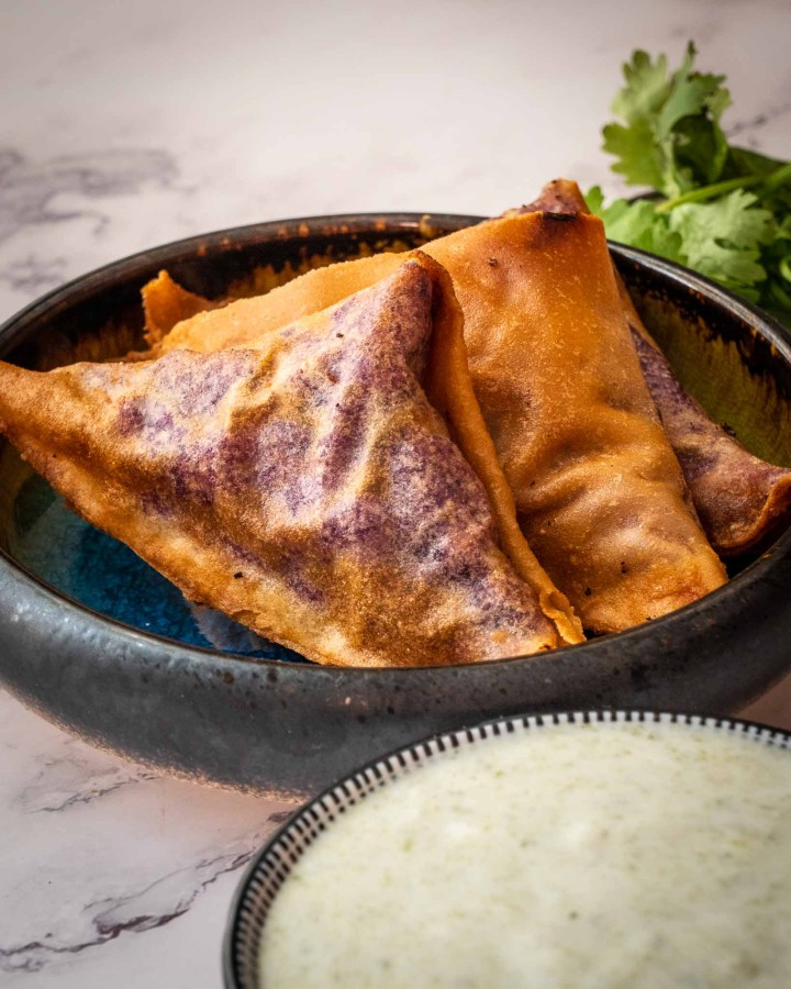 clay dish with row of 3 golden brown triangular samosas next to yoghurt dip and coriander on white marble table
