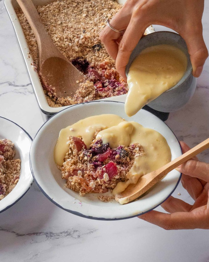 hand holding bowl filled with apple blackberry crumble pouring custard on top with wooden spoon atop a white marble table