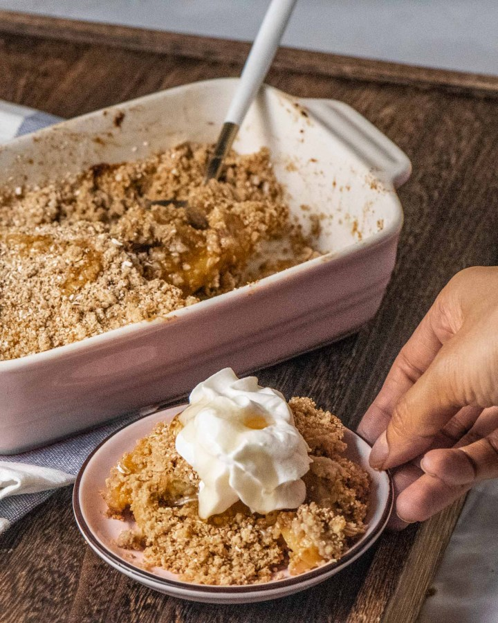 Pink rectangular rectangular baking dish filled with vegan apple crumble next to pink plate filled containing scoop of crumble and cream