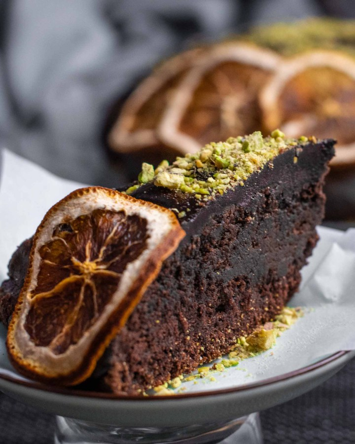 slice of moist chocolate orange cake topped with chocolate glaze, orange slices and crushed pistachios with large cake in background