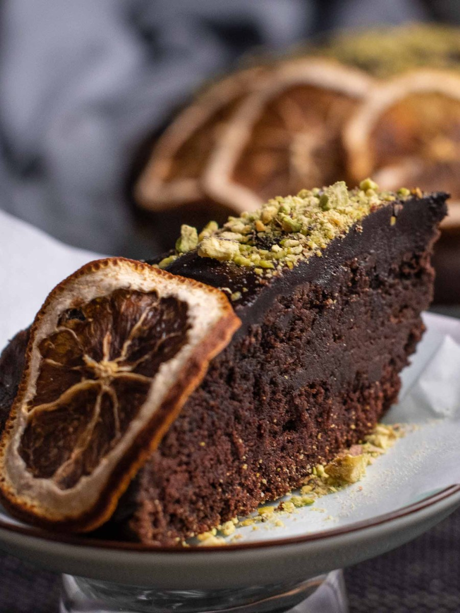 slice of chocolate orange cake topped in dried orange slices and crushed pistachios in front of large cake