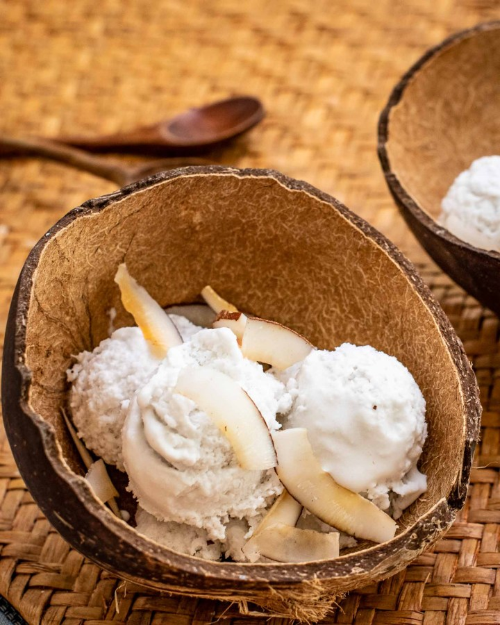 coconut bowl filled with scoops of vegan coconut ice cream and shredded coconut on woven straw mat