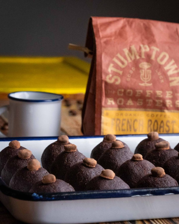 tray filled with rows of several  coffee chocolate protein balls topped with coffee beans next to bag of stumptown coffee and cup
