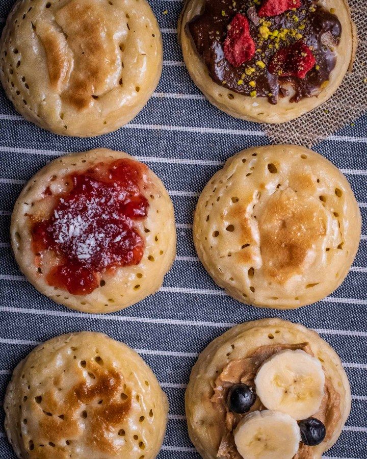 2 rows of circular toasted crumpets with either butter, jam, chocolate spread and nuts or peanut butter  with banana and blueberries