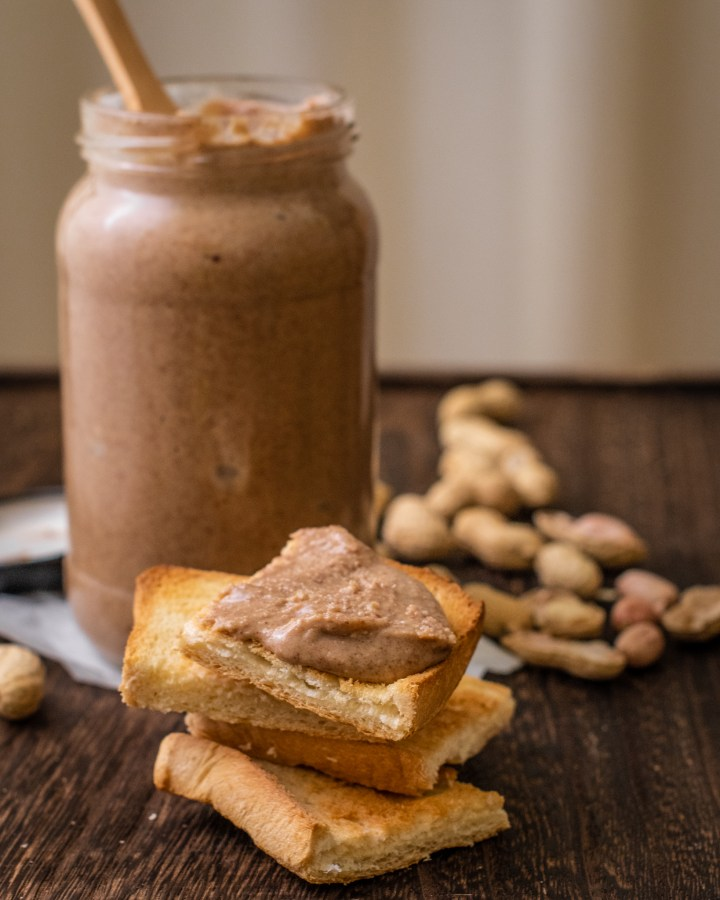 glass jar of homemade peanut butter next to slices of toast spread with peanut butter stacked next to loose peanuts on wooden table