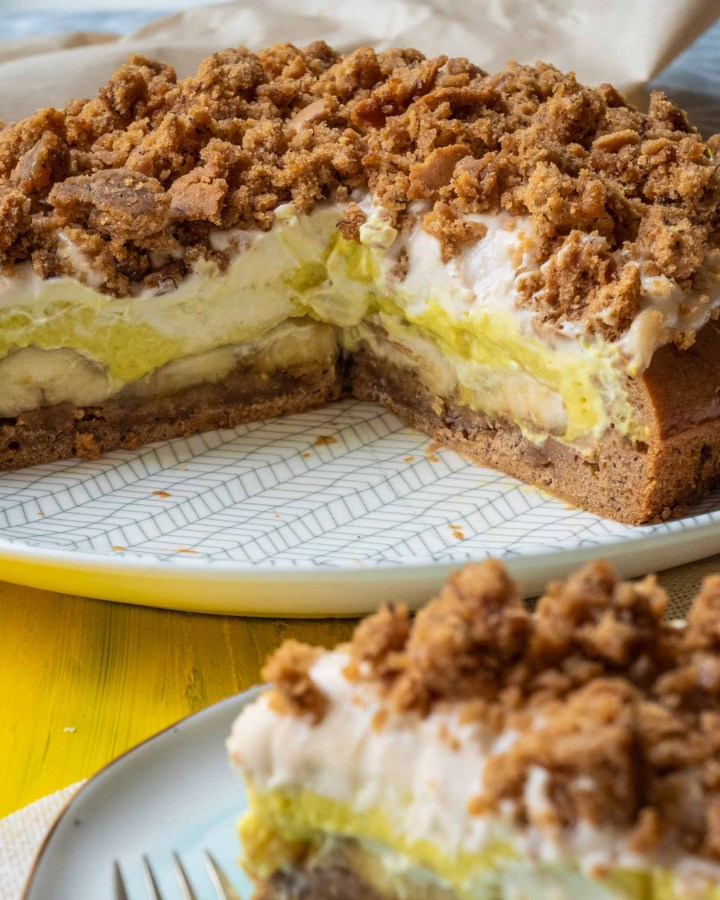 large banana cream german mole cake made of banana, cake, cream, custard and cake crumbles on top with slice in foreground