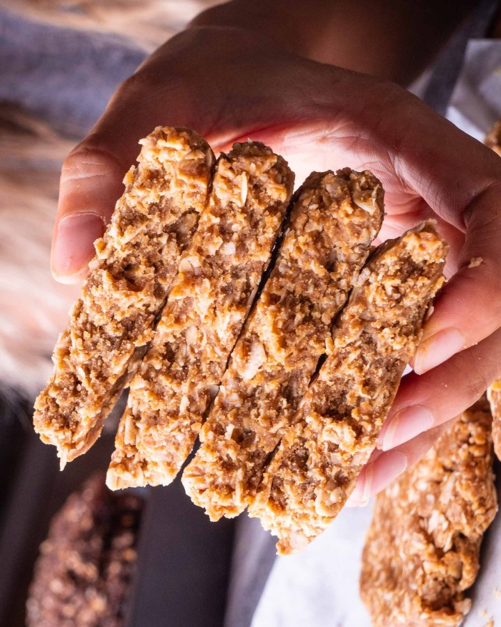 hand holding stack of oatmeal cookies all broken in half revealing crumbly, soft, chewy centres