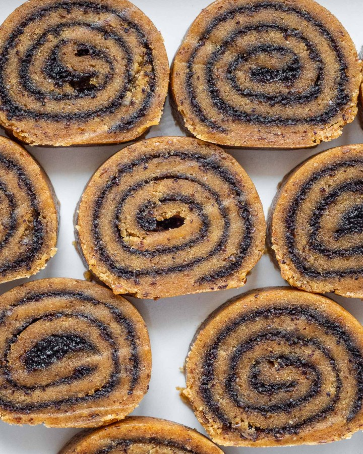 flatlay of golden brown sliced cinnamon roll swiss cake slices swirled with dark brown poppy seed jam inside