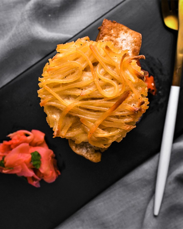 top view of round spaghetti bun sandwich next to pink ginger on black slate plate