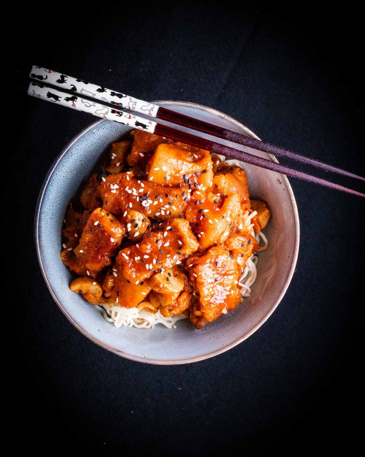 bowl of crispy sweet and sour tofu in red sticky sauce in stone bowl with wooden chopsticks on top on black table