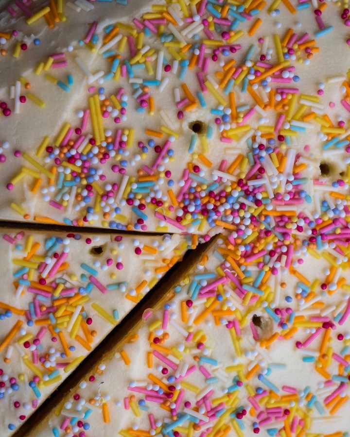 vegan cream cheese frosting on cake covered in multicoloured hundreds and thousands birthday cake sprinkles