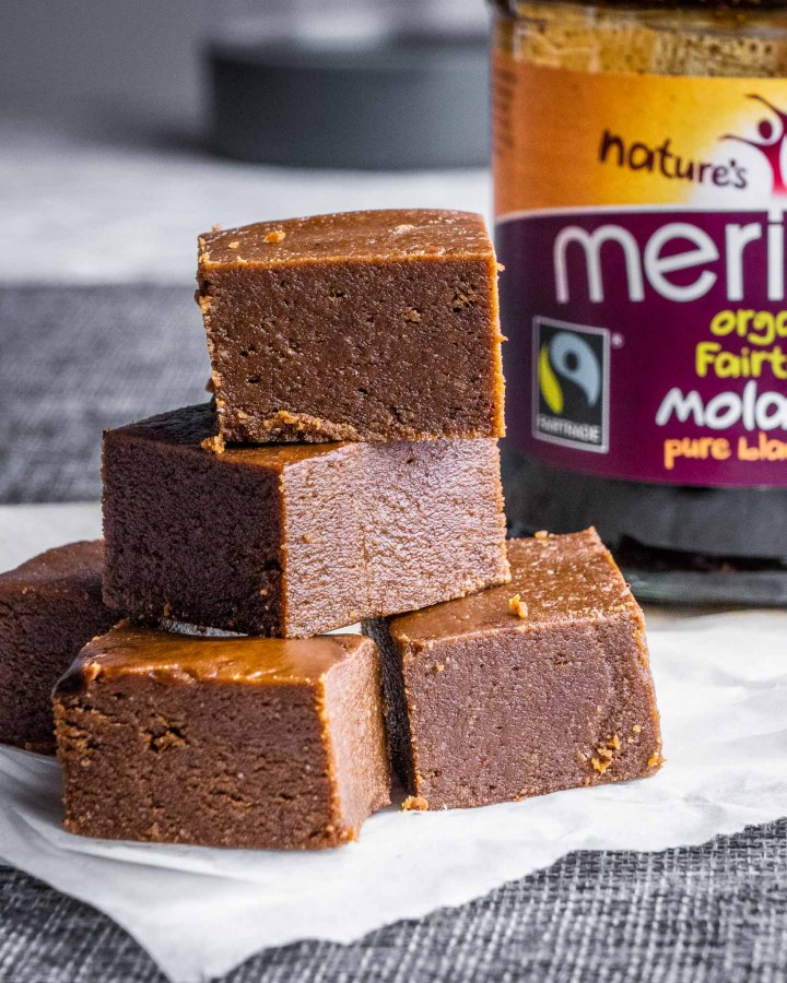 brown sticky healthy vegan gingerbread fudge chunks piled up in a stack on top of each other on a table with a jar of syrup behind them